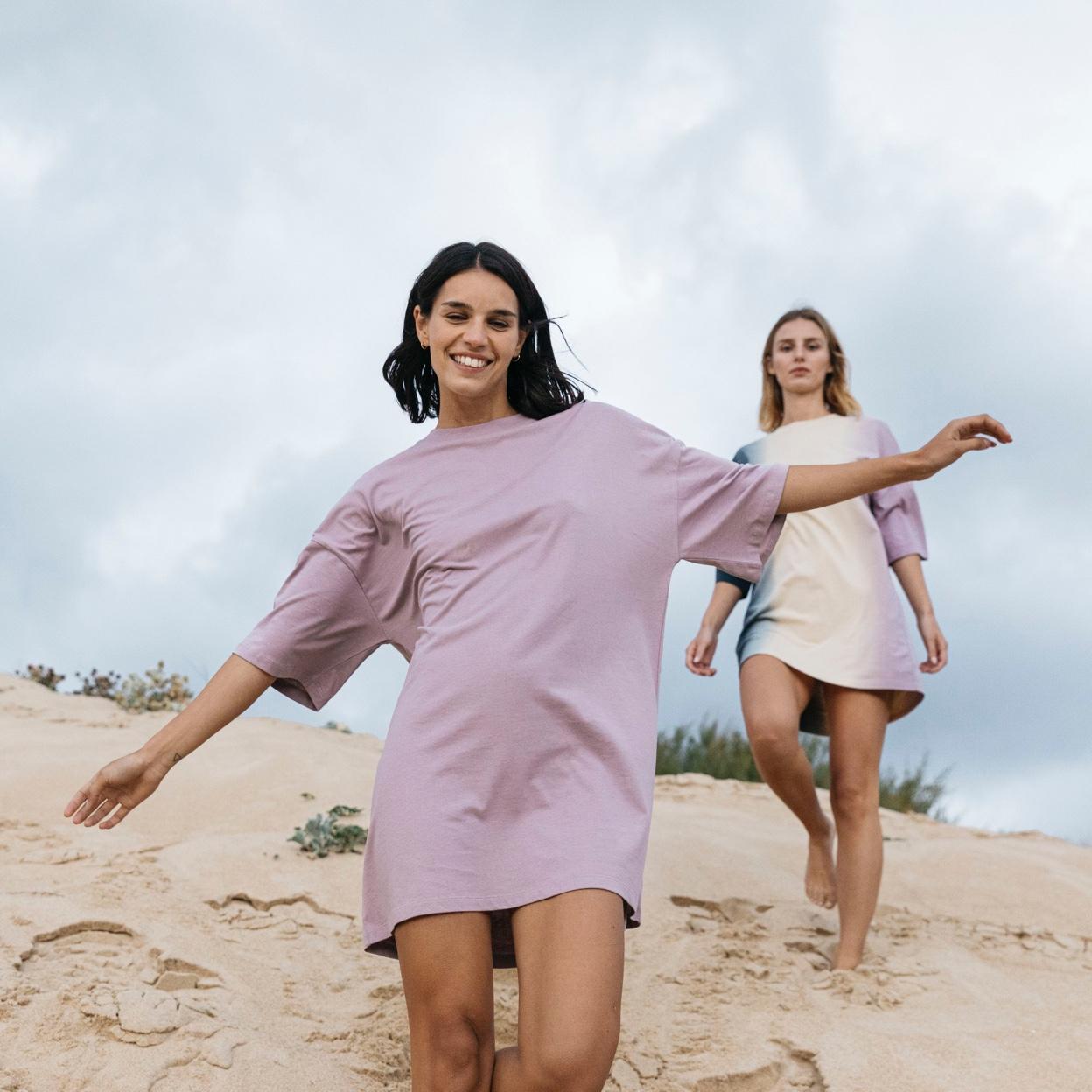 Visuel de deux femmes souriantes marchant dans le sable et portant les t-shirts robes de Stanley Stella