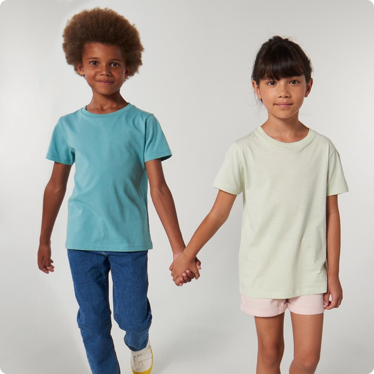 Visuel d'enfants qui portent des t-shirts personnalisables Stanley Stella et qui se tiennent la main comme pour exprimer le partenariat entre Stanley Stella et Mister Tee