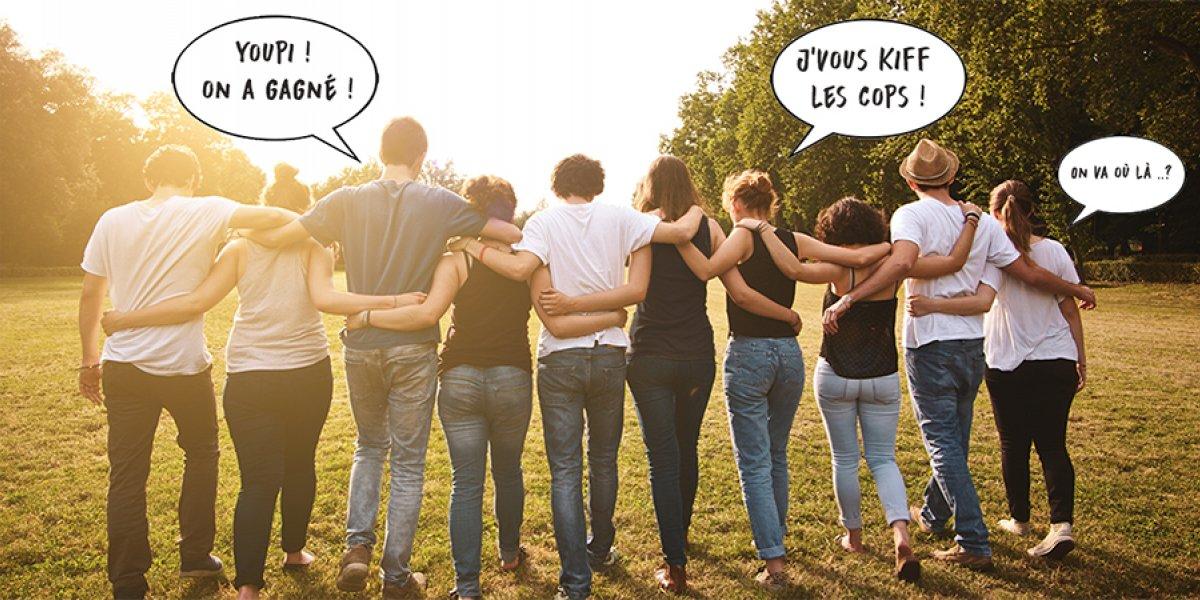 Un groupe d'amis étudiants marchent dans une prairie en se tenant par la taille et les épaules