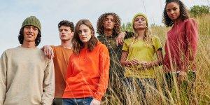 Six mannequins hommes et femmes posent dans sur une colline d'herbe en portant des sweats et t-shirts colorés de la marque Stanley/Stella