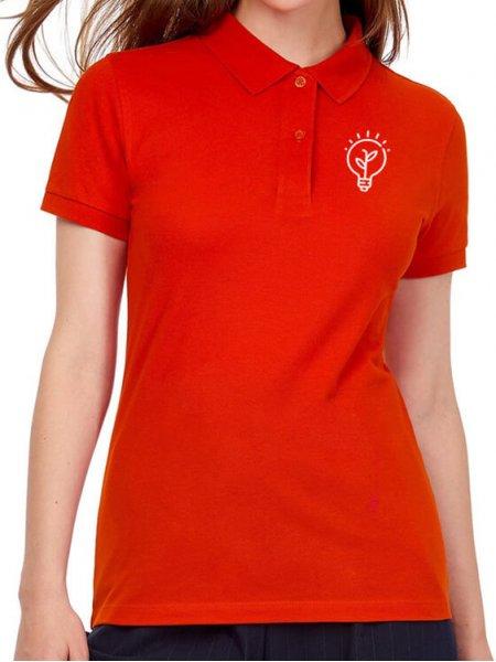 Le mannequin femme porte le polo CGPW440 en coton bio à personnaliser en coloris Fire Red