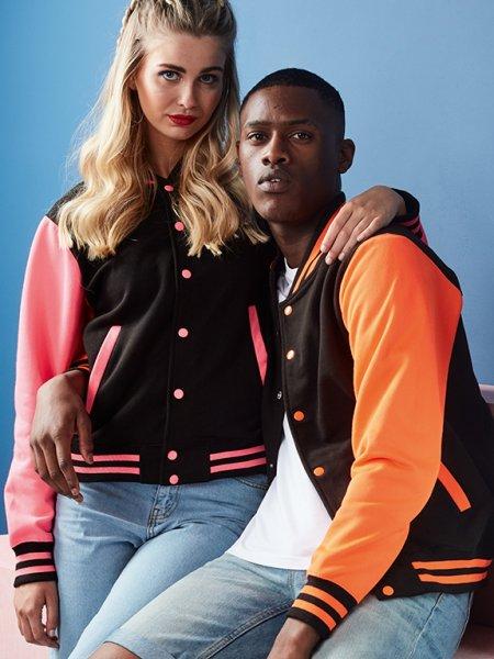 Les mannequins homme et femme portent la veste JH044 à manches contrastées fluo à personnaliser en coloris Jet Black Electric Pink et Jet Black Electric Orange