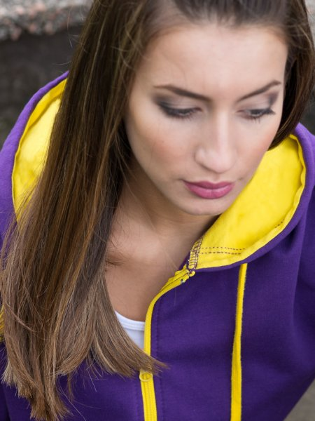 Le mannequin femme porte le sweat JH053 à capuche et zip contrastés à personnaliser en coloris Purple Sun Yellow
