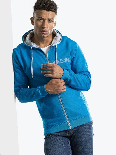Le mannequin homme porte le sweat à zip et capuche contrastés JH053 personnalisable en coloris Sapphire Blue Heather Grey
