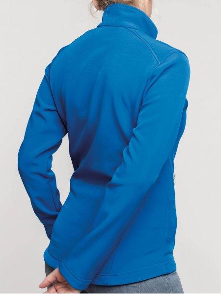 Le mannequin femme porte la veste softshell 2 couches K425 de dos à personnaliser en coloris Light Royal Blue