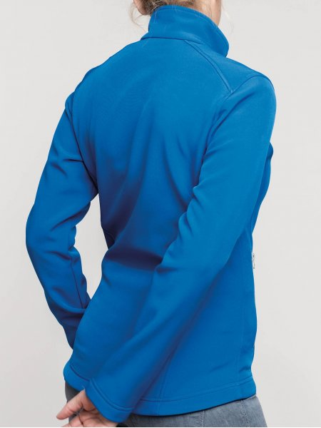 Le mannequin femme porte la veste softshell 2 couches K425 de dos à personnaliser en coloris Light Royal Blue