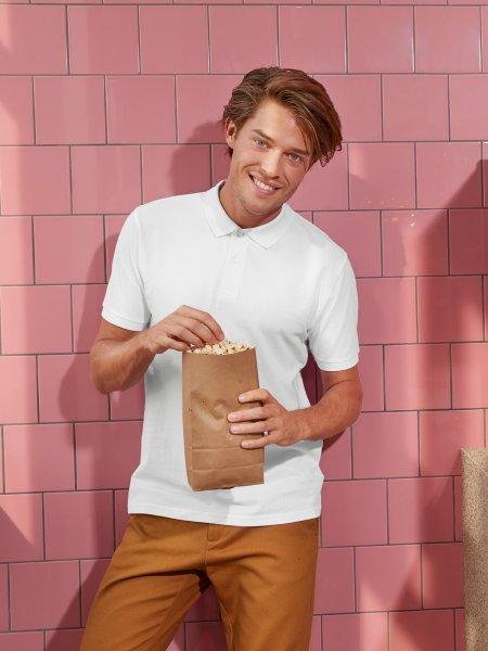 Le mannequin homme porte le polo CGPM430 en coton bio à personnaliser en coloris White