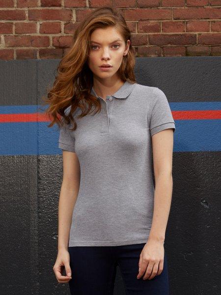 Le mannequin femme porte le polo CGPW440 en coton bio à personnaliser en coloris Heather Grey