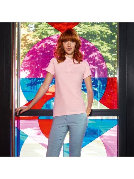 Le mannequin femme porte le polo CGPW440 en coton bio à personnaliser en coloris Orchid Pink