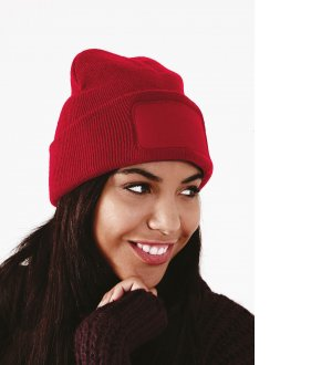 Le mannequin porte le bonnet patch B445 à personnaliser en coloris Classic Red